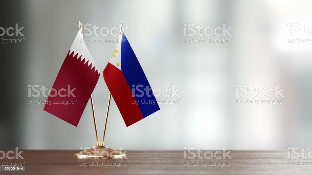 Qatar y Filipinas bandera par en un escritorio sobre fondo Defocused - foto de stock