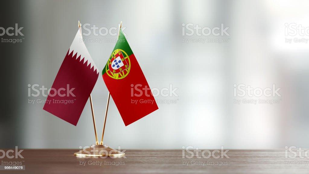 Bandera de Qatar y Portugal par en un escritorio sobre fondo Defocused - foto de stock