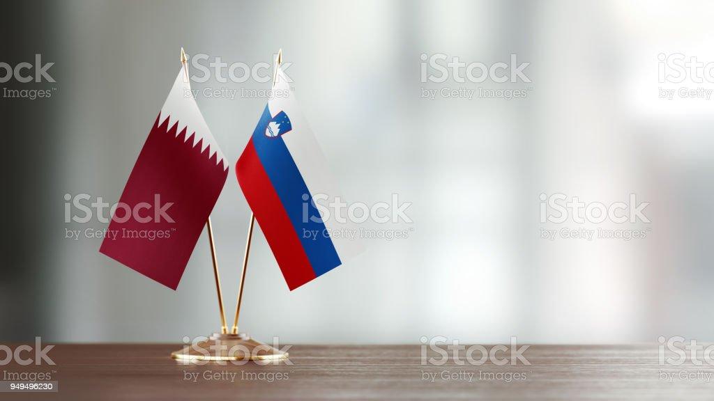 Qatar y par de bandera eslovena en un escritorio sobre fondo Defocused - foto de stock