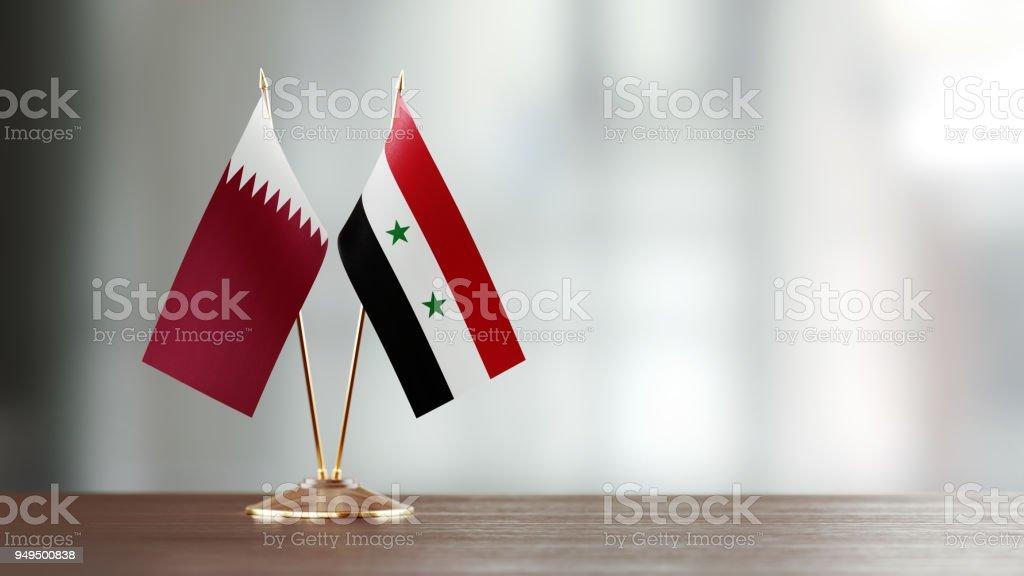 Qatar y Siria bandera par en un escritorio sobre fondo Defocused - foto de stock