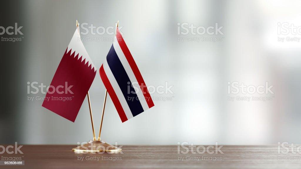 Par de bandera qatarí y tailandesa en un escritorio sobre fondo Defocused - foto de stock