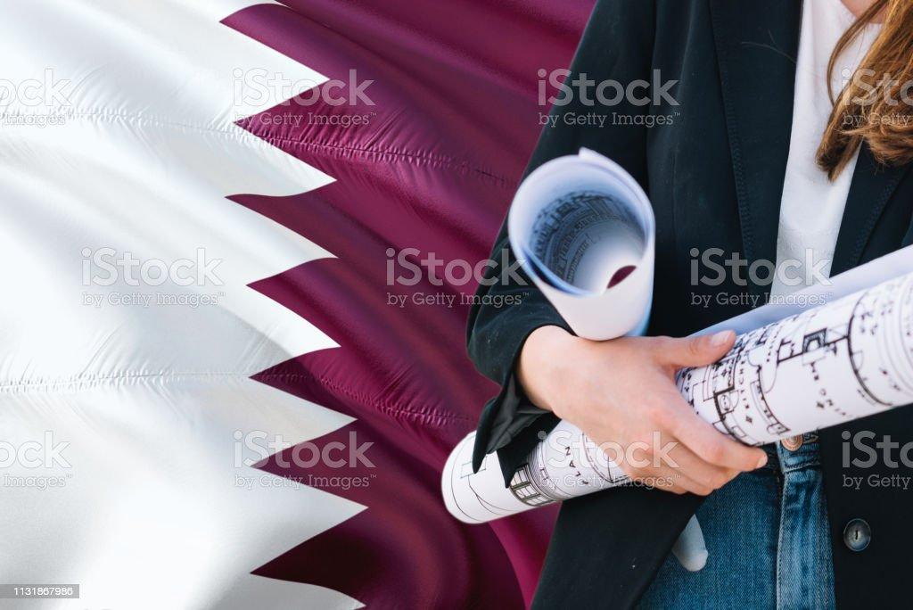 Mujer de QATARI Architect sosteniendo el plano contra Qatar agitando el fondo de la bandera. Concepto de construcción y arquitectura. - foto de stock