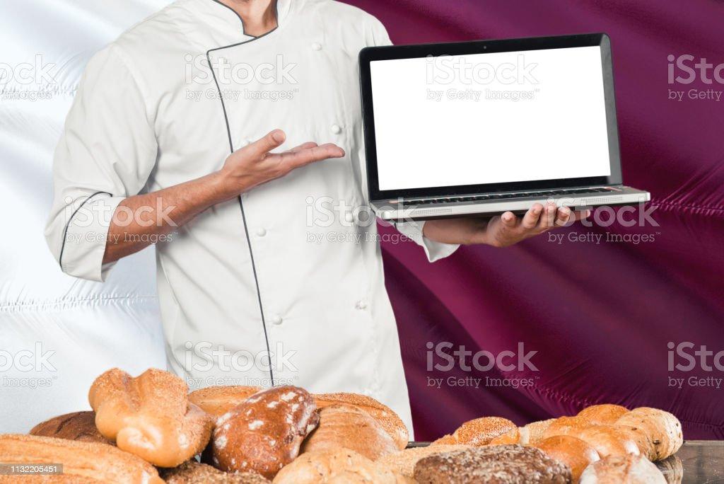 QATARI Baker sosteniendo portátil en Qatar bandera y panes de fondo. Chef usando uniforme señalando la pantalla en blanco para el espacio de copia. - foto de stock