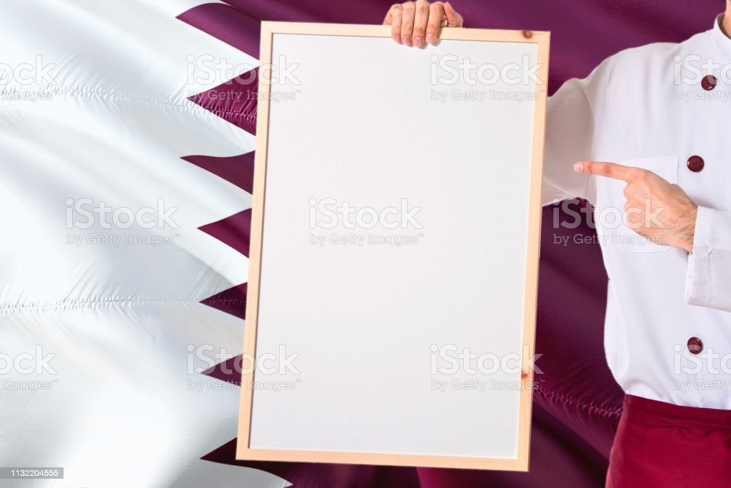 Chef QATARI sosteniendo el menú de pizarra en blanco en el fondo de la bandera de Qatar. Cocine usando un espacio de señalización uniforme para el texto. - foto de stock