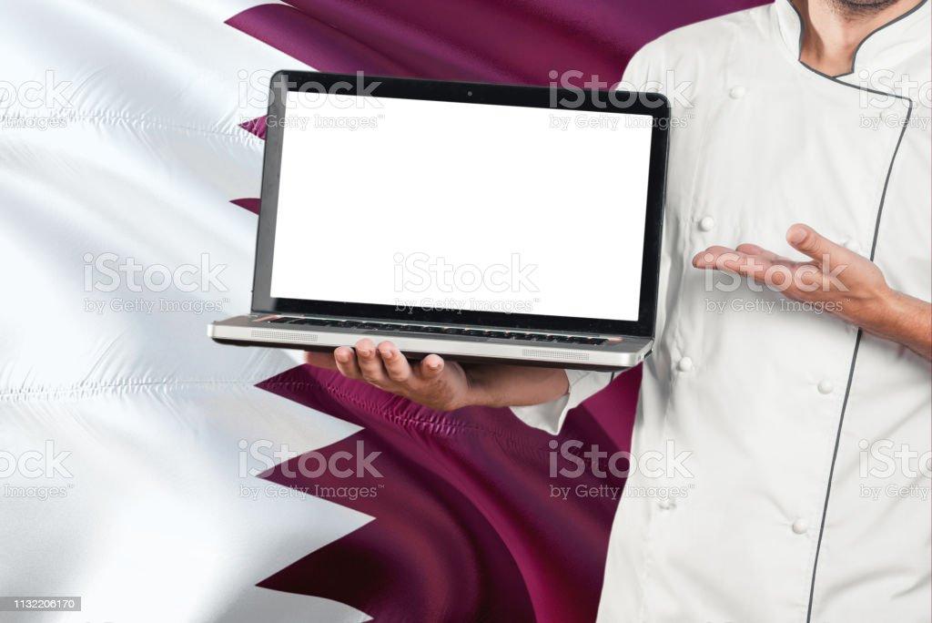 QATARI chef sosteniendo portátil con pantalla en blanco en el fondo de la bandera de Qatar. Cocine usando uniforme y apuntando el ordenador portátil para el espacio de la copia. - foto de stock