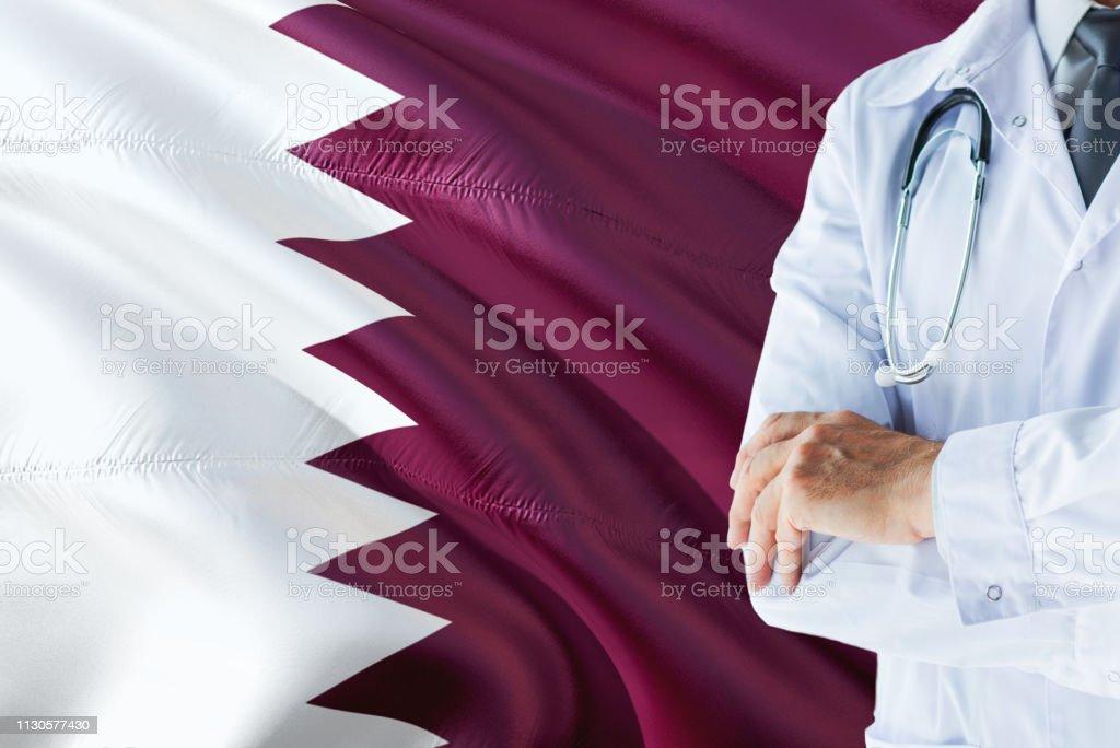 Qatarí médico con estetoscopio sobre fondo de bandera de Qatar. Concepto de sistema nacional de salud, tema médico. - foto de stock