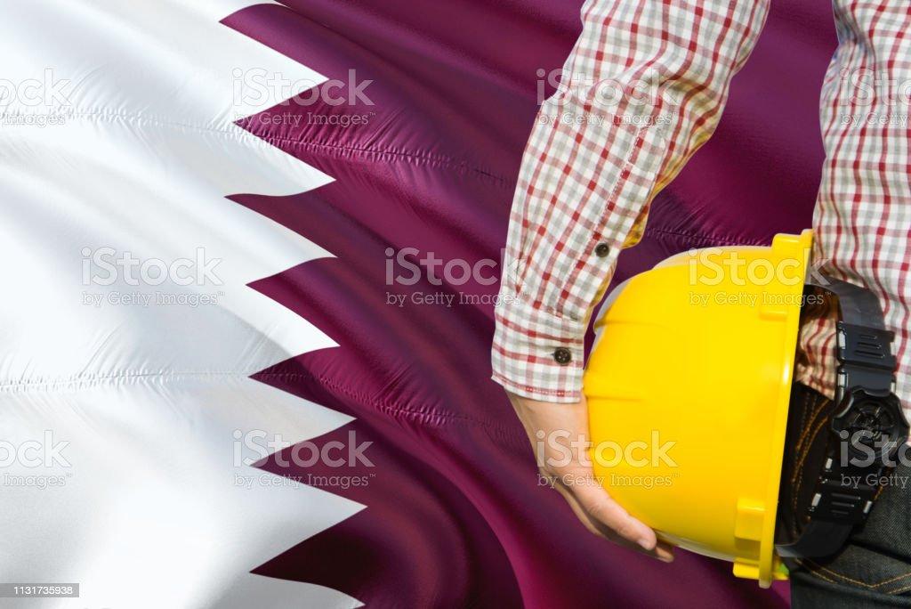 El ingeniero QATARI está sosteniendo el casco de seguridad amarillo con el fondo de la bandera de Qatar. Concepto de construcción y edificación. - foto de stock
