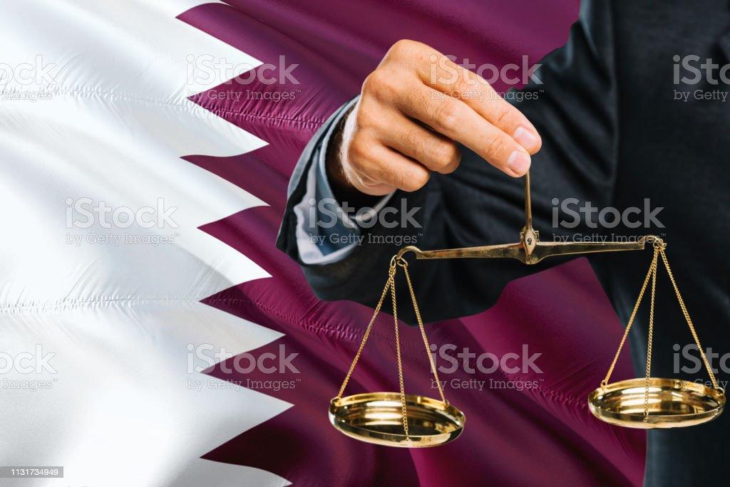 El juez QATARI está sosteniendo escalas doradas de justicia con Qatar agitando el fondo de la bandera. Tema de igualdad y concepto legal. - foto de stock