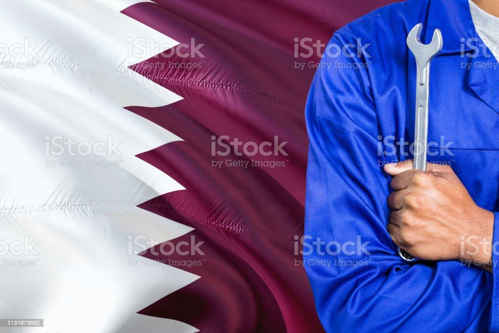 Mecánico de Qatar en el uniforme azul está sosteniendo la llave contra agitar fondo de la bandera. Técnico de armas cruzadas. - foto de stock