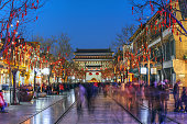 Leading out from Archery Tower of Qianmen, Beijing, China the Qianmen street's history dates back 570 years with its many shops and restaurants. Twilight picture facing the tower featuring Chinese New Year decorations.