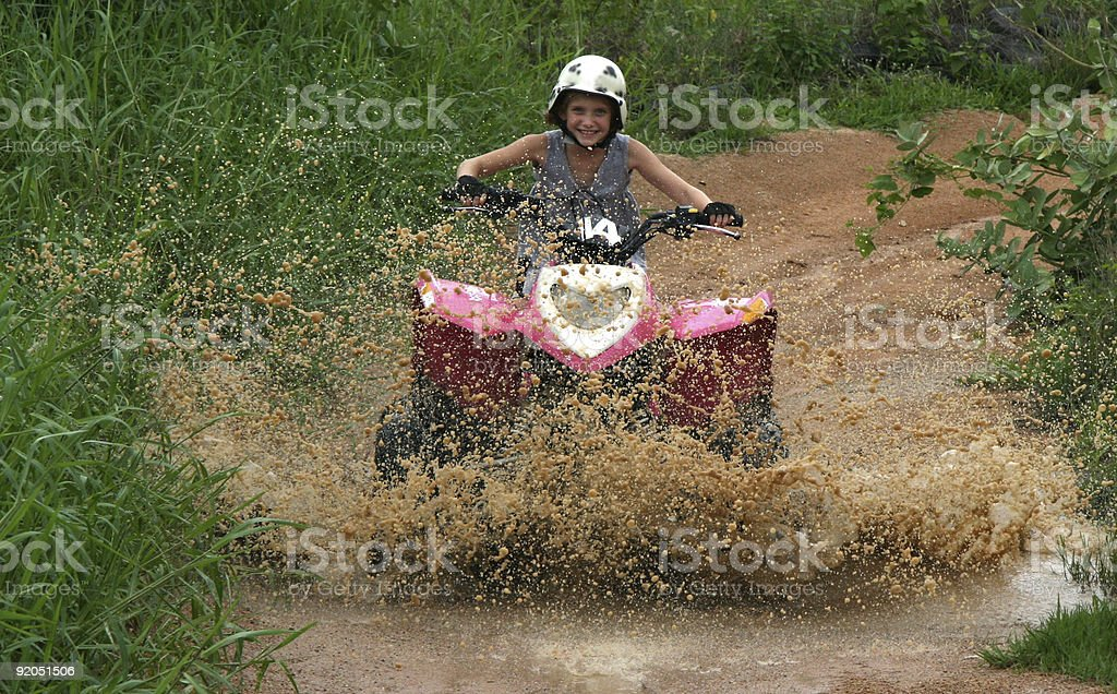 Quad Bike Mud Fun with a Smiling Young Girl stock photo