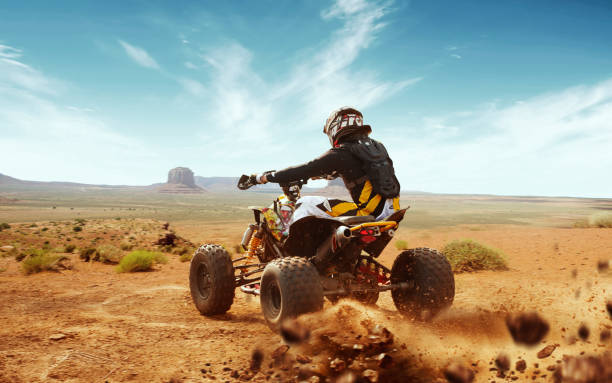 Quad bike. Quad bike in dust cloud, sand quarry on background. ATV Rider in the action. quadbike stock pictures, royalty-free photos & images
