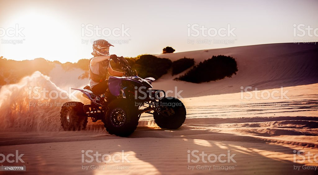 Quad bike racer in protective gear driving on sand dunes stock photo