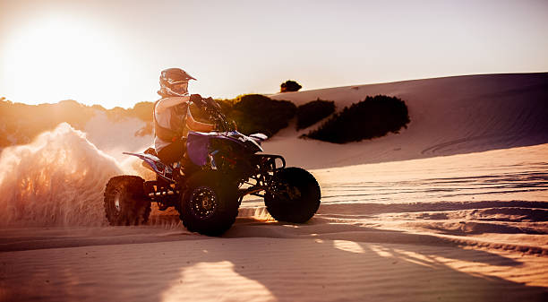 Quad bike racer in protective gear driving on sand dunes Professional quad bike racer driving on sand dunes in protective gear quadbike stock pictures, royalty-free photos & images