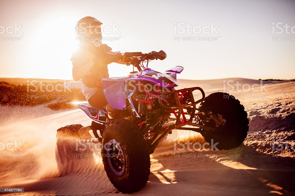 Quad biker in desert race with sun flare behind stock photo