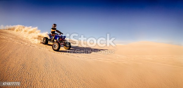 Professional quad biker racing downhill over a sand dune in a desert race