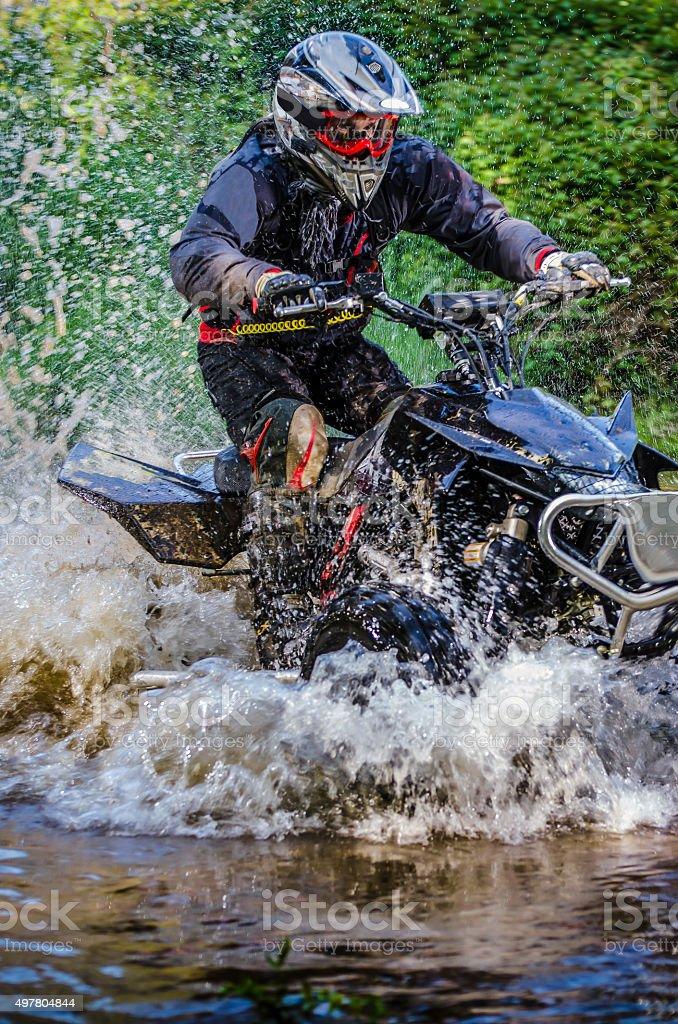Quad rider through water stream stock photo