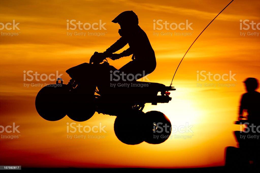 Quadbike jumping at sunset royalty-free stock photo