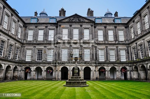 Edinburgh, Scotland, UK - May 27, 2018: Built in the late 17th century, Palace of Holyroodhouse is Her Majesty The Queen's official residence in Scotland. The quadrangle centre court is beautifully groomed.