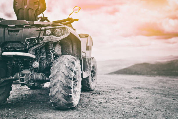 Quadricycle or quad bike on the mountains background on a cloudy day in black and white toned stock photo