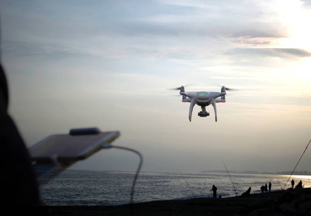 quadrocopter drone flying at sky when people fishing at beach stock photo