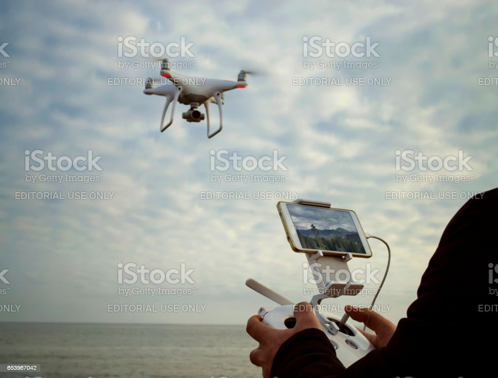 quadrocopter drone take 4k video to landscape with remote control unit at man hands stock photo