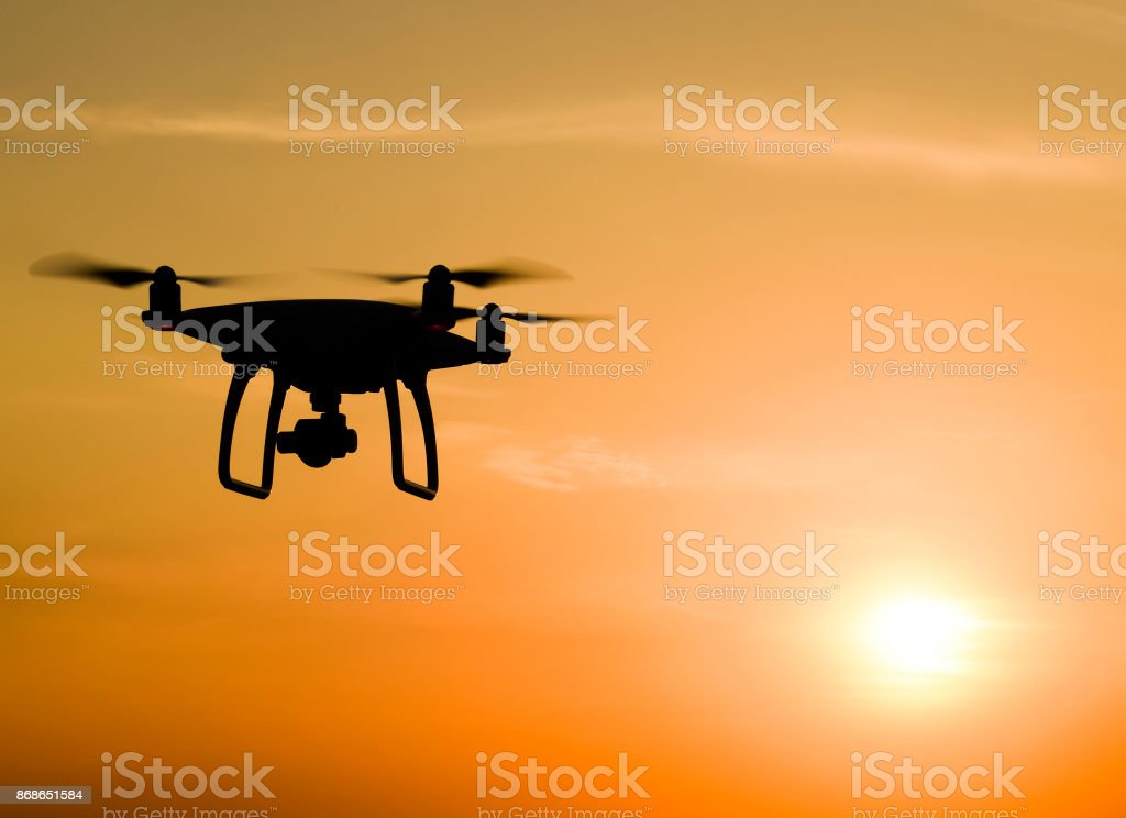 Quadrocopters silhouette against the background of the sunset stock photo