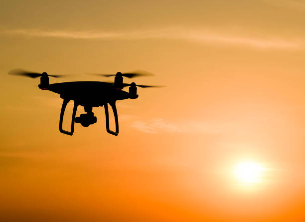 quadrocopters silhouette against the background of the sunset - drones stock photos and pictures