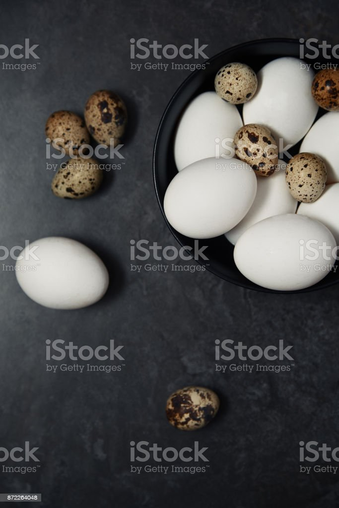 Quail and chicken eggs on a table stock photo