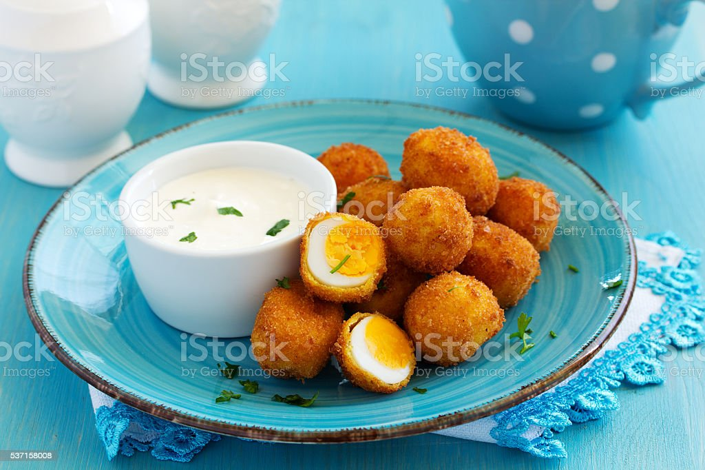 Quail eggs, deep fried with white sauce. stock photo