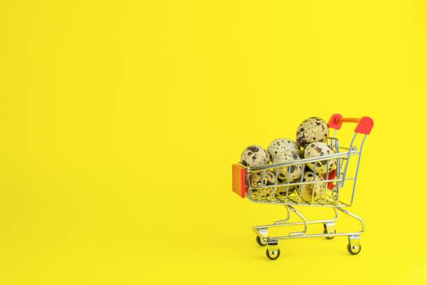 wachteleier in einem einkaufswagen auf gelbem hintergrund - wachtelei stock-fotos und bilder