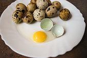 ウズラの卵を、白のプレート。卵 1 個が破損しています。