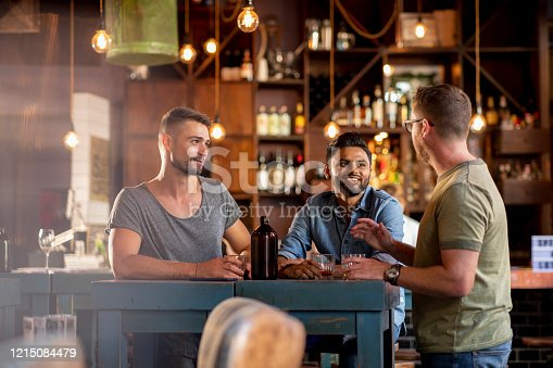 A side view of a group of male friends having a drink and talk together in a bar in Perth, Australia.