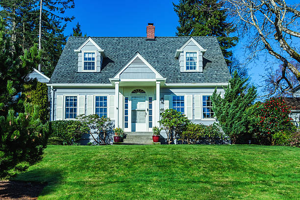 Quaint Cape Cod Style House Photo of a quaint American Cape Cod Style home on a sunny day with clear blue sky and green grass. cape cod stock pictures, royalty-free photos & images