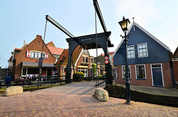 Quaint Dutch architecture Lifting canal bridge and traditional Dutch houses, Volendam, Netherlands bascule bridge stock pictures, royalty-free photos & images