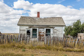 istock quaint little old abandoned house sitting behind broken wood fence 512041023