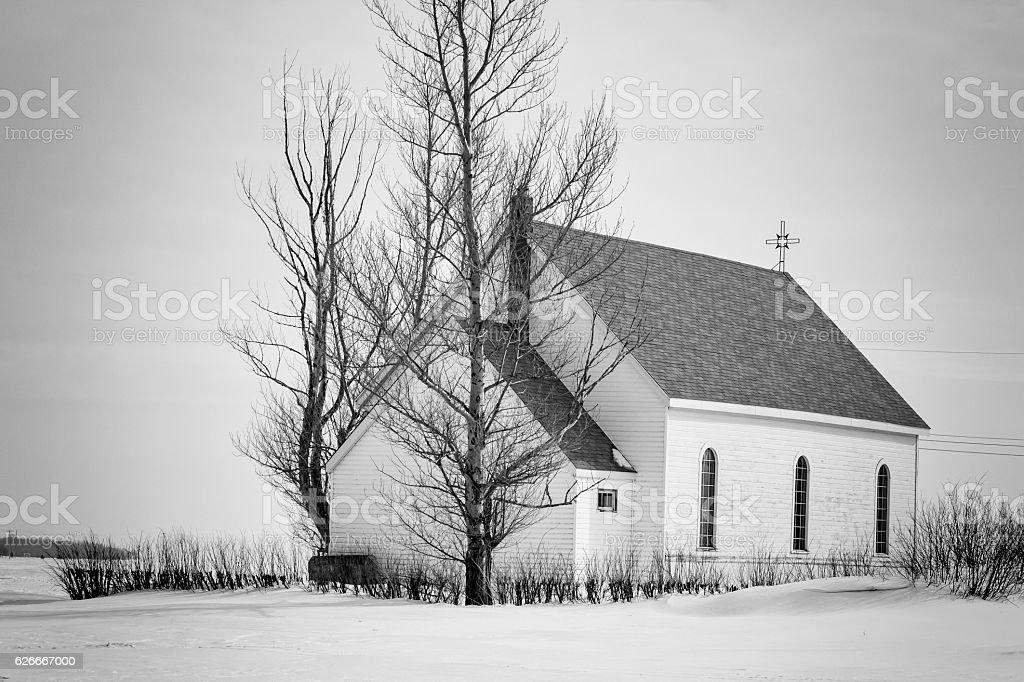 quaint little white church sitting on blanket of snow. stock photo