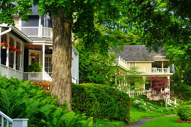 Quaint old homes Quaint old homes line a tree-shaded street in an older neighborhood inn stock pictures, royalty-free photos & images