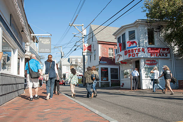 Quaint Provincetown. Provincetown, USA -  October 18, 2014: People wander along Commercial Street enjoying a summer day and the shops. A small quaint tourist town on Cape Cod. provincetown stock pictures, royalty-free photos & images