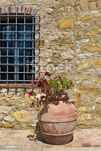 A still life of an old fashion terra cotta flower pot planted with flower in front of an old building in arural town in the Chianti wine region of Tuscany, Italy.