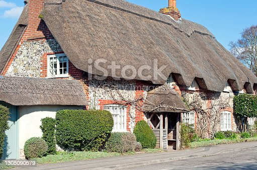 Quaint traditionally thatched cottage near Old Sarum Hill fort, Salisbury, Wiltshire, England, UK. Clear blue skies and crisp winter days outdoors typify an English February in Wiltshire where the colours of the clearly defined medieval and ancient architecture stand out as historical landmarks in the scenic countryside and beautiful town