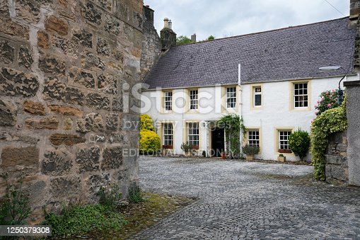 Culross, Scotland, UK - June 13, 2019: Quiet narrow street with large white building with yellow framed windows on a cobblestone lane in the tiny little medieval village in the Kingdom of Fife, Scotland, Europe