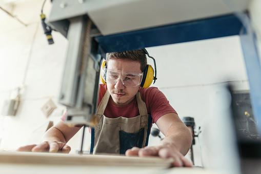 istock Qualified carpenter working on grinding machine 1162302526