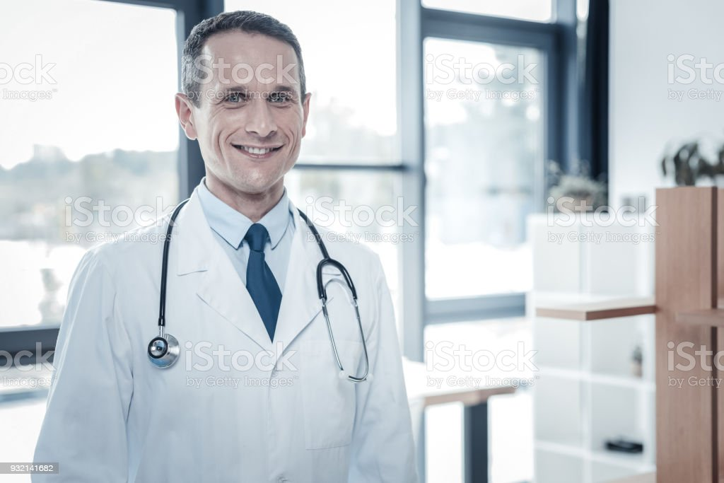 Qualified confident doctor feeling good himself and smiling. stock photo