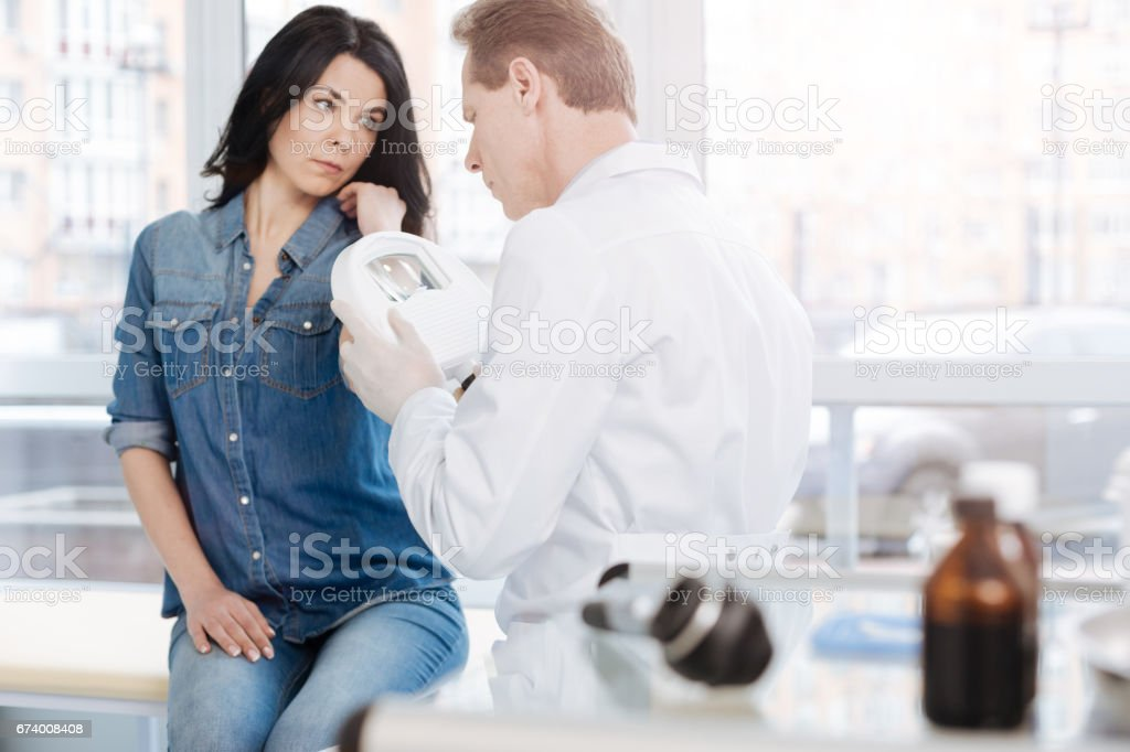 Qualified dermatologist using medical loupe for skin examination indoors royalty-free stock photo