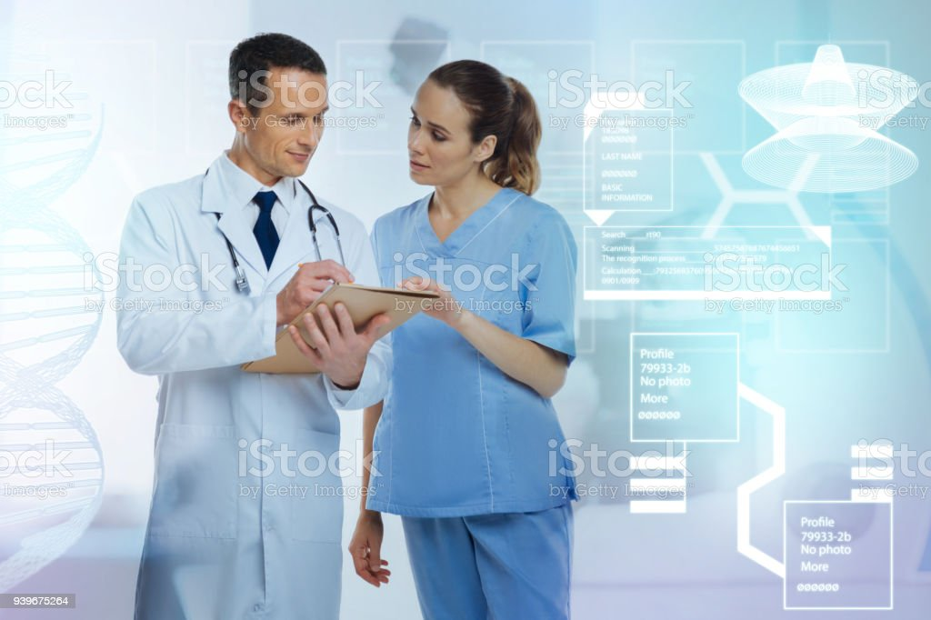 Qualified doctor showing the nurse a medical history of a new patient stock photo