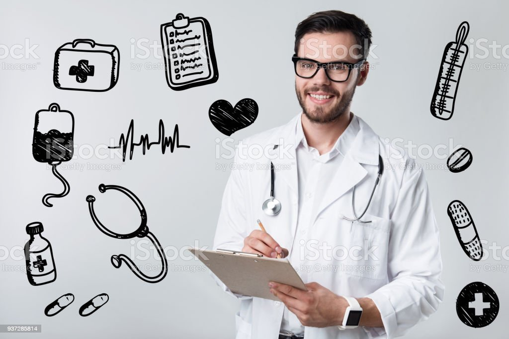 Qualified doctor smiling while writing a prescription to his patient stock photo
