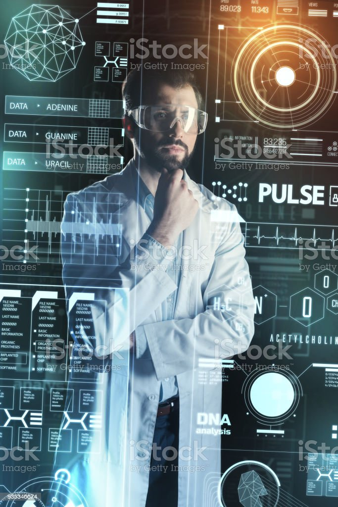 Qualified doctor touching his beard while standing alone and thinking stock photo