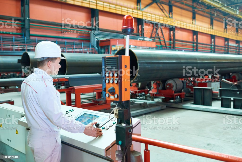 Qualified factory employee setting up machine stock photo