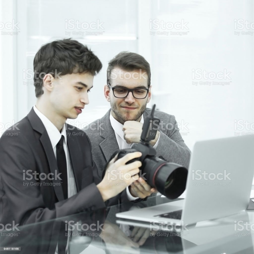 qualified photographers choose photos to upload files to their laptops stock photo